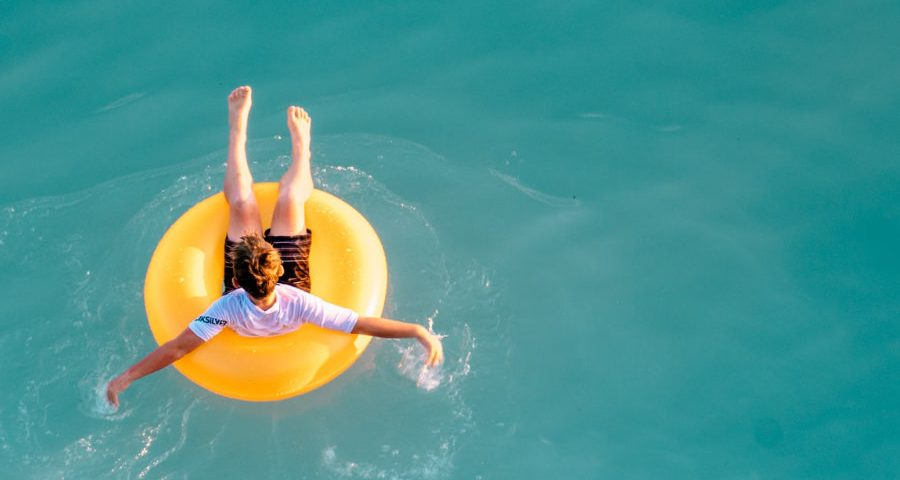 άνθρωπος μέσα σε κίτρινο φουσκωτό σωσίβιο στη θάλασσα