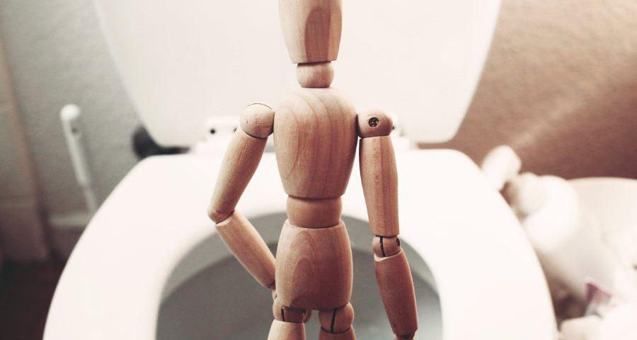 ξύλινο μοντέλο ανθρώπου που ουρεί μπροστά σε λεκάνη