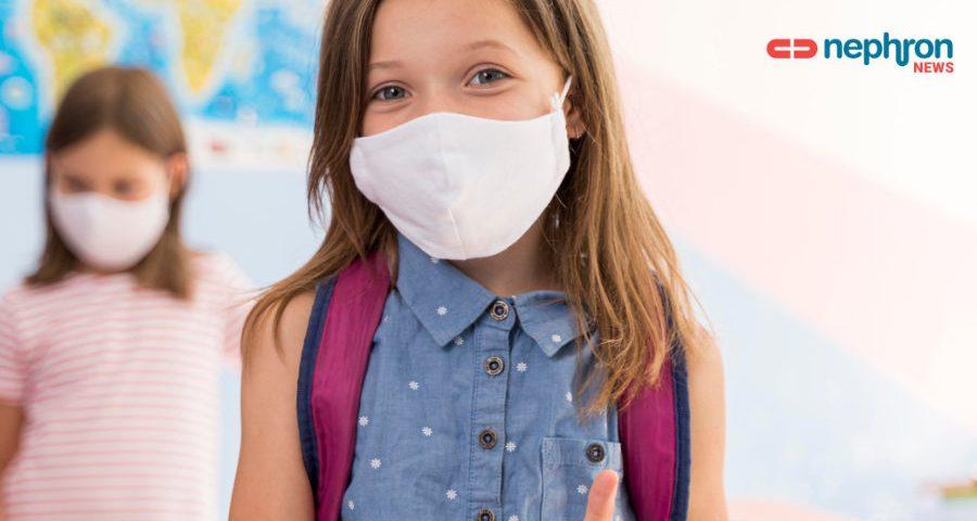χαρούμενη μαθήτρια σε σχολείο φοράει μάσκα