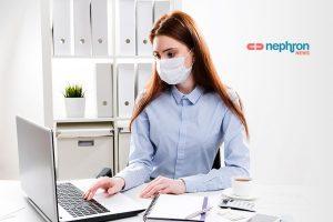 νεαρή γυναίκα δουλεύει στον υπολογιστη φορώντας μάσκα
