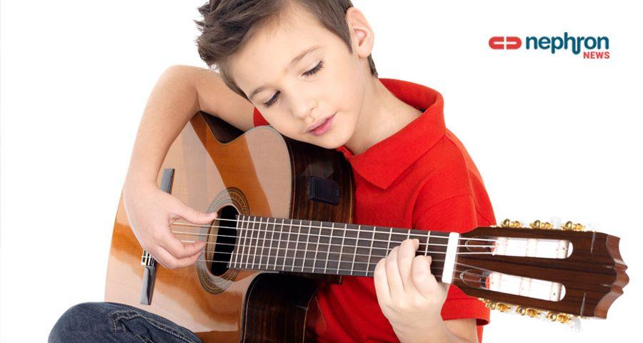αγόρι με κόκκινη μπλούζα παίζει κιθάρα